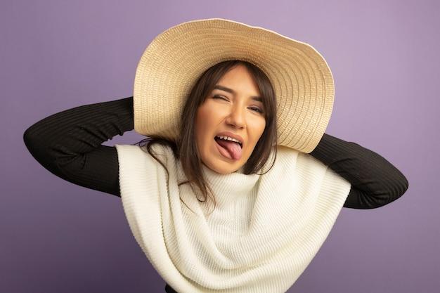 흰색 스카프와 여름 모자와 젊은 여자는 보라색 벽 위에 서있는 혀를 튀어 나와 행복하고 쾌활한 전면을보고