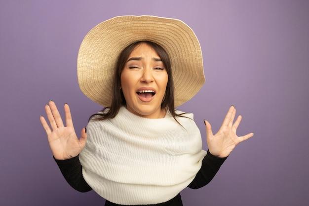 Молодая женщина с белым шарфом и летней шляпой, глядя вперед, кричит с поднятыми руками, испугавшись, стоя у фиолетовой стены