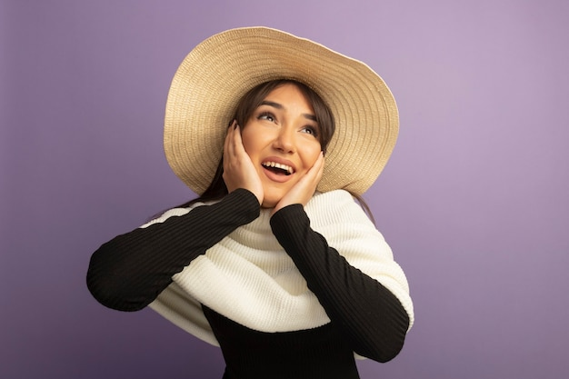 흰색 스카프와 여름 모자와 젊은 여자가 그녀의 얼굴에 팔을 올려 행복하고 긍정적 인 미소를 찾고