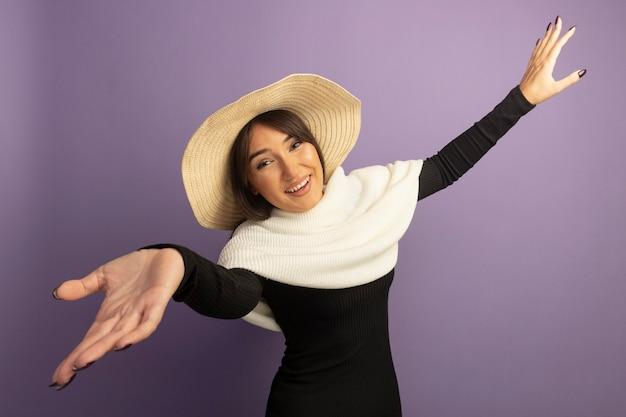 흰색 스카프와 여름 모자 넓은 여는 손으로 환영 제스처를 만드는 젊은 여자