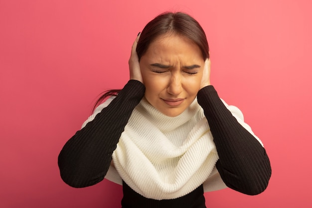 イライラした表情で両手で耳を閉じる白いスカーフを持つ若い女性