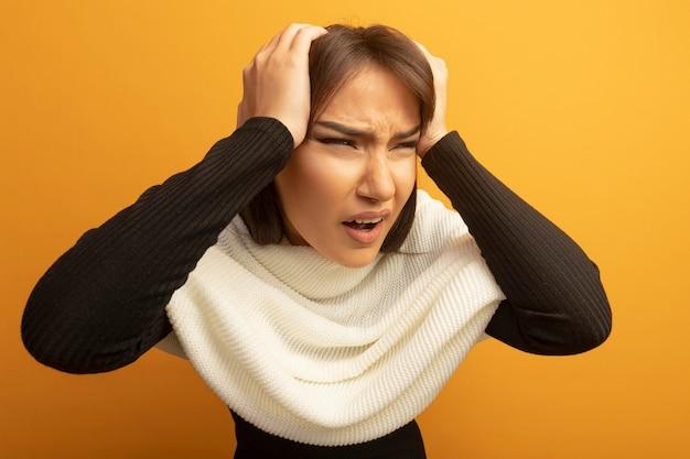 白いスカーフを持つ若い女性は、間違いのために彼女の頭の上の手で混乱し、不満を持っています
