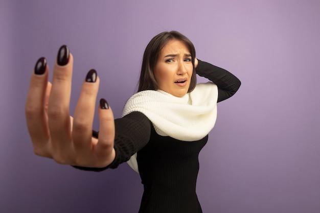 白いスカーフを持つ若い女性は混乱し、腕を出して非常に心配しています