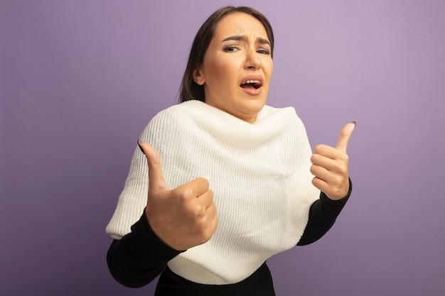 白いスカーフを持つ若い女性は親指を上に表示して混乱