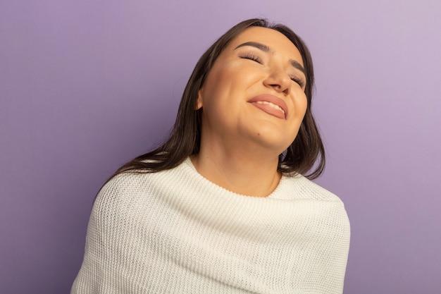 Giovane donna con sciarpa bianca felice e positiva che ride fuori