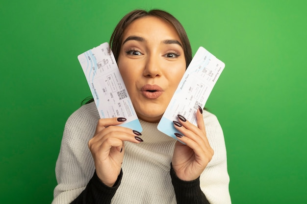 Young woman with white scarf holding air tickets with happy face smiling
