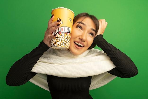 Giovane donna con sciarpa bianca che tiene secchio con popcorn alzando lo sguardo sorridente confuso con la mano sulla sua testa in piedi sopra la parete verde
