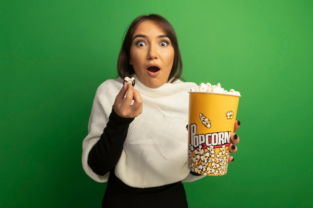 Young woman with white scarf holding bucket with popcorn surprised and amazed