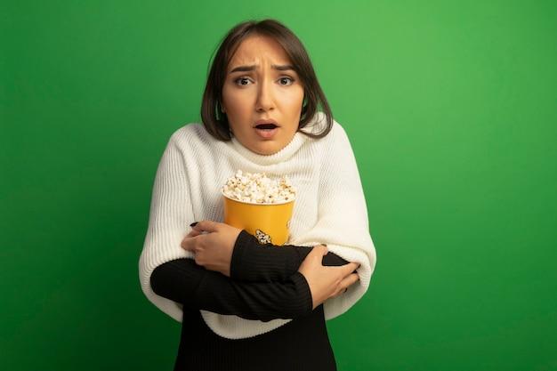 Giovane donna con sciarpa bianca che tiene secchio con popcorn preoccupato e confuso