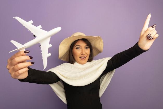검지 손가락으로 가리키는 장난감 비행기 행복하고 밝은 미소를 보여주는 여름 모자에 흰색 스카프와 젊은 여자
