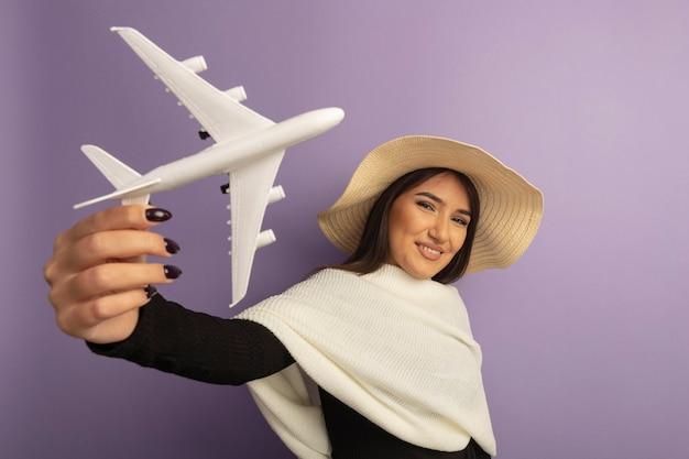 행복하고 밝은 미소를 보여주는 장난감 비행기를 보여주는 여름 모자에 흰색 스카프로 젊은 여자