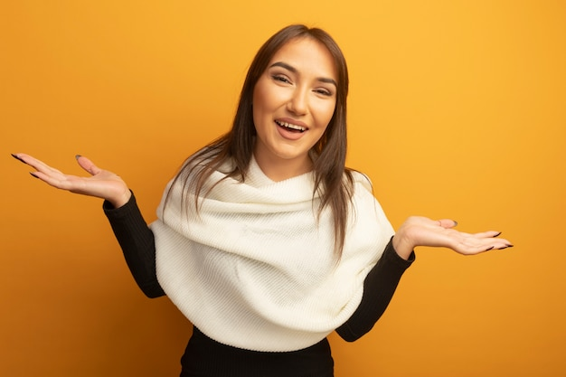 Young woman with white scarf looking at front smiling spreading arms to the side standing over orange wall