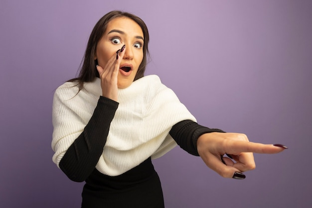 Young woman with white scarf looking surprised pointing with index finger at something telling a secret with hand nera mouth