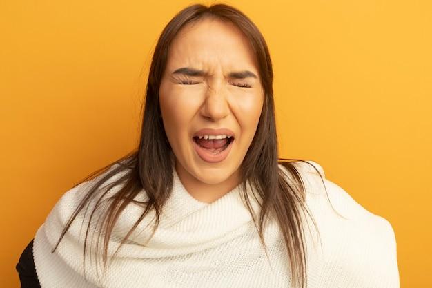 Giovane donna con sciarpa bianca che grida con espressione infastidita con gli occhi chiusi