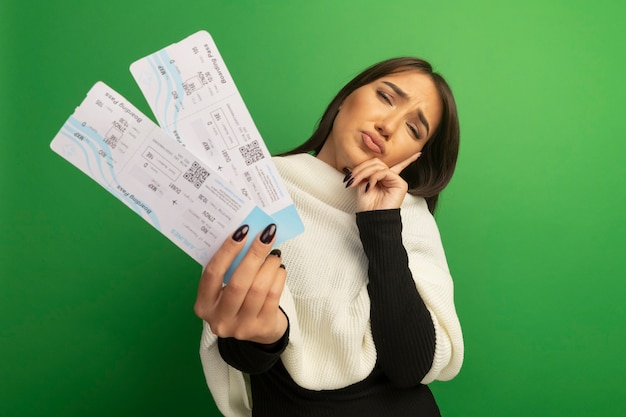 Giovane donna con sciarpa bianca che mostra i biglietti aerei confusa e molto ansiosa