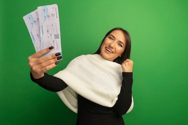 그녀의 성공을 기뻐하는 행복하고 쾌활한 떨림 주먹 항공권을 보여주는 흰색 스카프와 젊은 여자