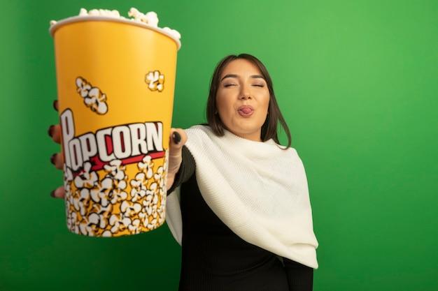 Giovane donna con sciarpa bianca che mostra secchio con popcorn felice e allegro che attacca fuori la lingua