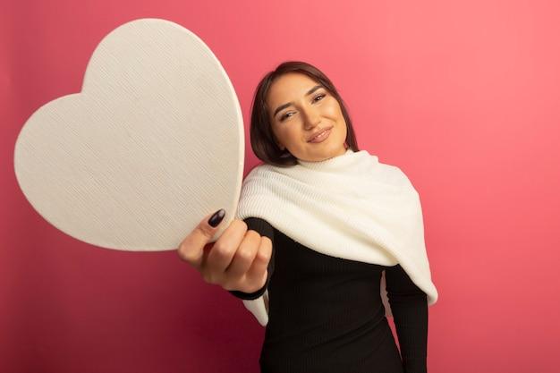 段ボールの心を元気に笑っている白いスカーフを持つ若い女性