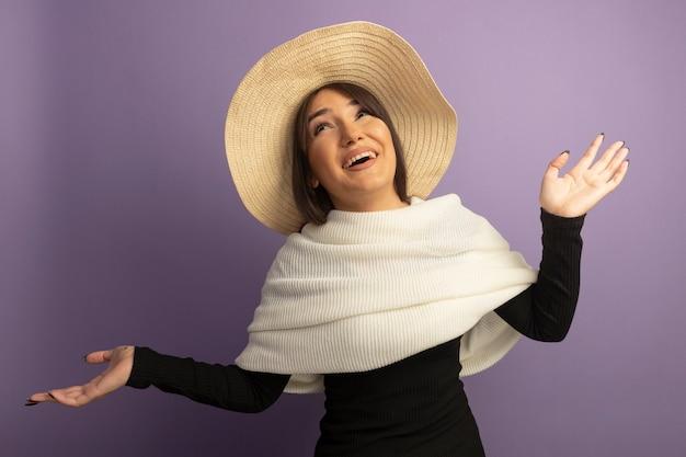 Giovane donna con sciarpa bianca e cappello estivo sorridente felice e allegro con la faccia felice in piedi sul muro viola
