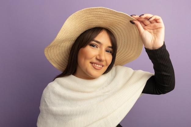 Giovane donna con sciarpa bianca e cappello estivo guardando davanti felice e positivo toccando il suo cappello in piedi sul muro viola