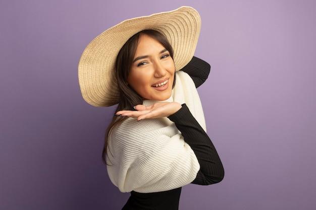 Giovane donna con sciarpa bianca e cappello estivo sorridendo serenamente felice e positivo