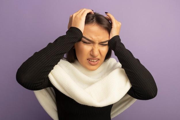 Giovane donna con sciarpa bianca che tocca la sua testa che sembra malata soffre di mal di testa