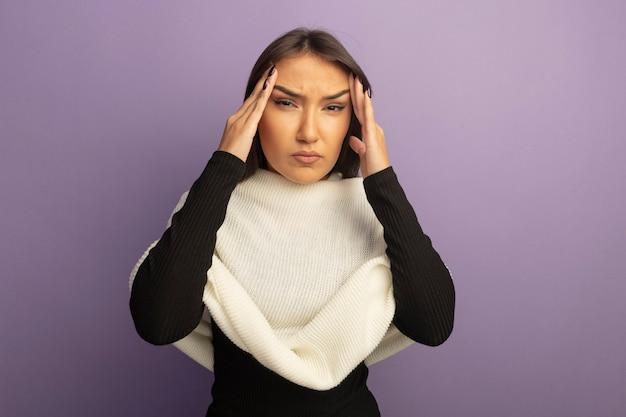 Giovane donna con sciarpa bianca che tocca le sue tempie che sembrano indisposte avendo mal di testa