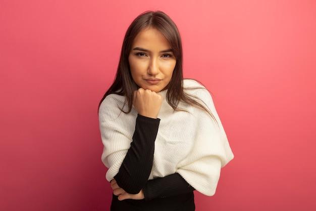 真面目な顔の思考とあごに手で白いスカーフを持つ若い女性