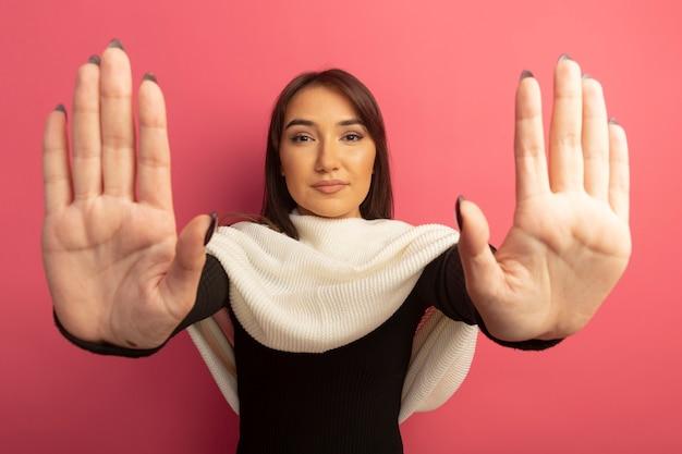 開いた手で停止ジェスチャーを作る深刻な顔を持つ白いスカーフを持つ若い女性