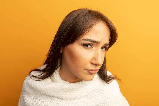 Giovane donna con sciarpa bianca con espressione scettica