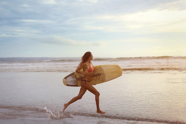 A young woman with white surfing in her hands running along the ocean shore at sunset.