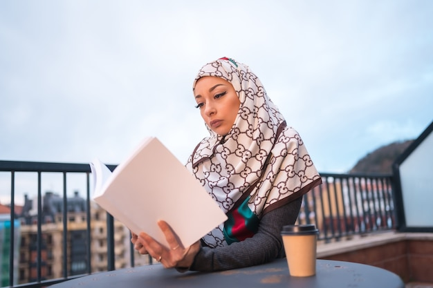 Young woman with white veil at the computer on the terrace of a coffee shop, reading a beautiful book