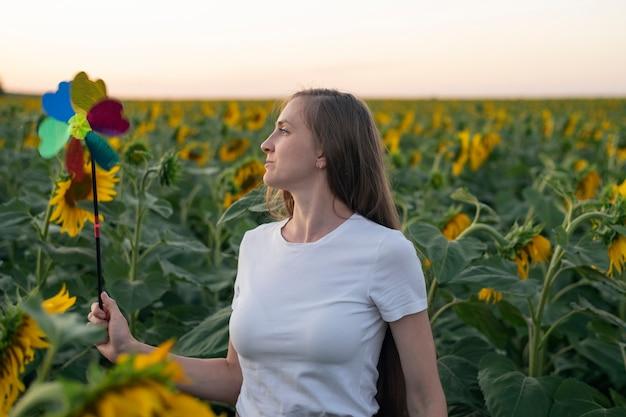 風車のおもちゃを持った若い女性がひまわり畑を歩きます。代替エネルギー。グリーンエネルギーの概念。