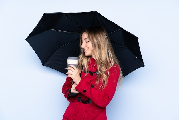 Young woman with winter coat holding an umbrella and a coffee to take away
