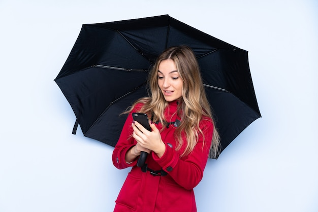 Young woman with winter coat holding an umbrella and a mobile
