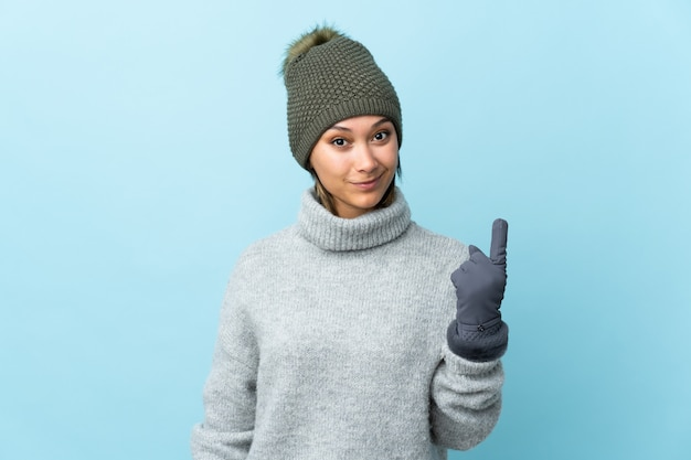 Young  woman with winter hat isolated on blue space pointing with the index finger a great idea