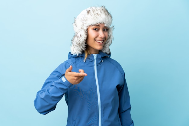 Young  woman with winter hat isolated on blue space points finger at you