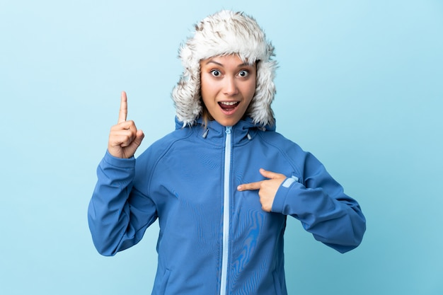 Young  woman with winter hat isolated on blue space with surprise facial expression