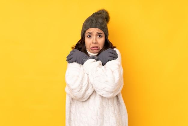 Молодая женщина в зимней шапке изолировала замораживание