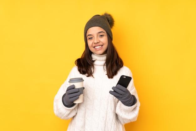 Молодая женщина в зимней шапке изолирована, держа кофе на вынос и мобильный телефон