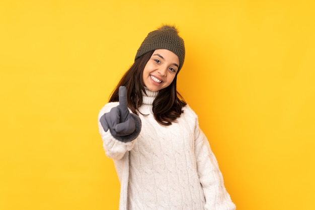 Young woman with winter hat isolated howing and lifting a finger