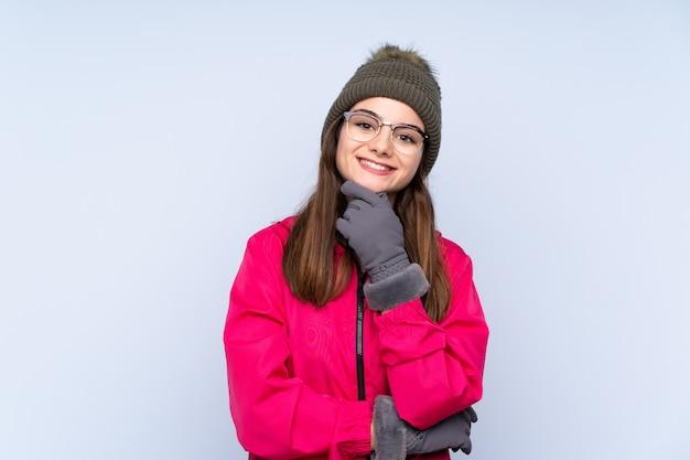 겨울 모자와 젊은 여자 안경 파란색 벽에 고립 된 미소