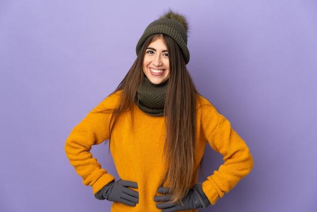 보라색 벽에 고립 된 겨울 모자와 젊은 여자 엉덩이에 팔을 포즈와 미소