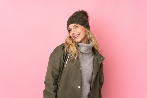 Young woman with winter hat isolated on pink wall laughing and looking up