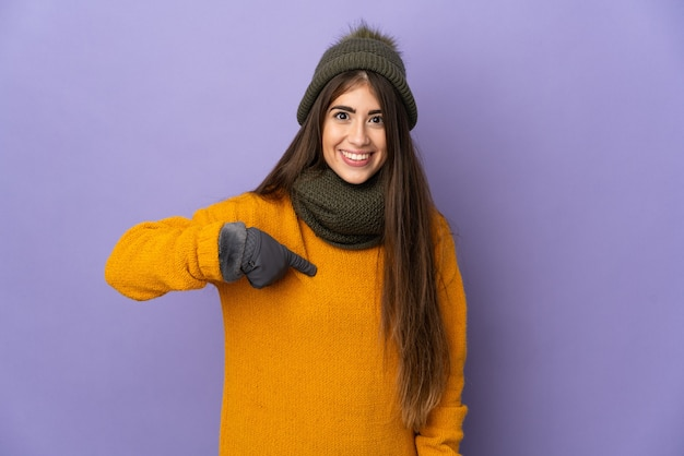 Young woman with winter hat isolated on purple wall with surprise facial expression