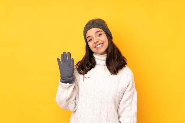 冬の帽子を持つ若い女性は幸せな表情で手で敬礼を分離しました