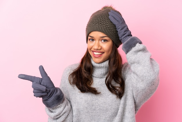 Young woman with winter hat over isolated wall