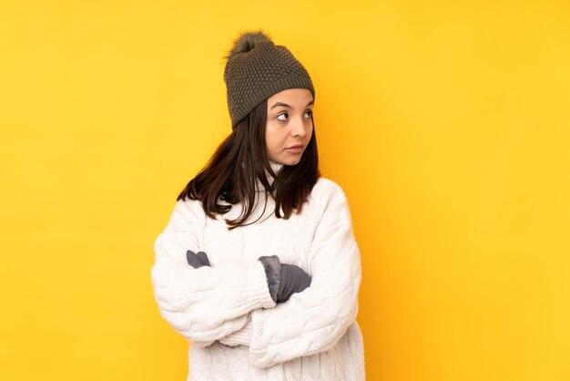 겨울 모자 고립 된 노란색 배경 초상화와 젊은 여자
