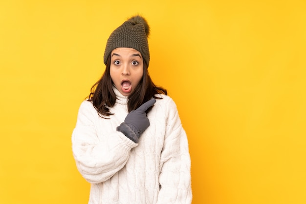 Young woman with winter hat over isolated yellow wall surprised and pointing side