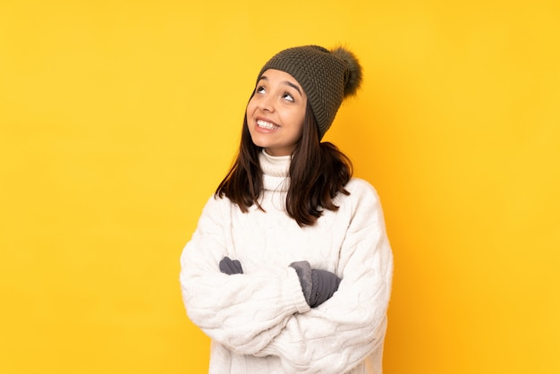 Young woman with winter hat looking up while smiling